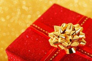 Ein Weihnachtsgeschenk vor goldenem Weihnachtsdeko Hintergrund