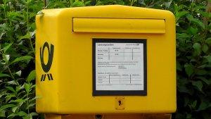 """Mit Weihnachtspostkarten """"Frohe Weihnachten"""" wünschen - Ein gelbes Schild mit schwarzem Text - Briefkasten"""